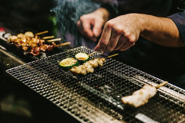 Mãos de close-up de japonês yakitori chef grelhando frango marinado com gengibre, alho e molho de soja.