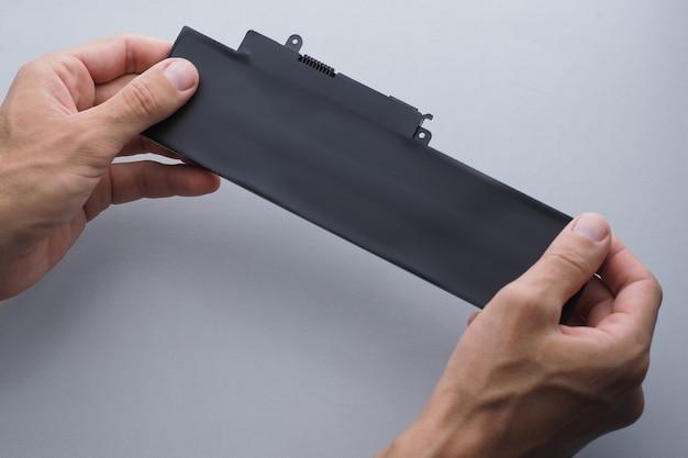 Mãos de close-up de remoção de bateria segurando uma bateria de laptop nova