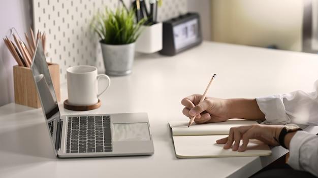 Mãos de close-up, escrevendo em papel de caderno