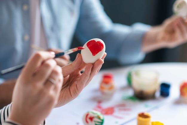 Mãos de close-up, pintura de ovo para a páscoa