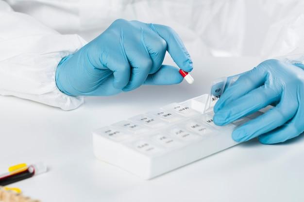 Mãos de close-up, segurando a caixa de comprimidos com cápsulas