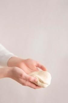 Mãos de close-up, segurando a massa