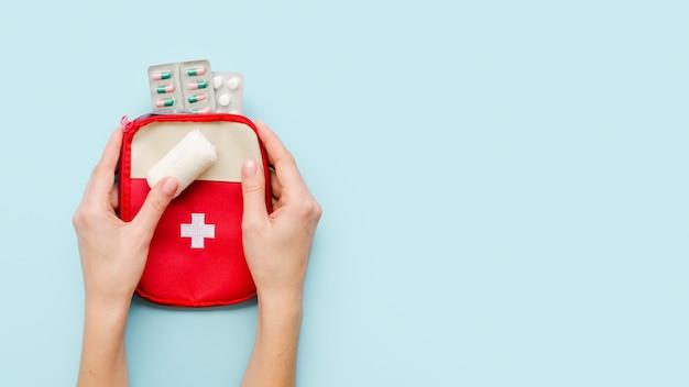 Mãos de close-up, segurando o kit médico