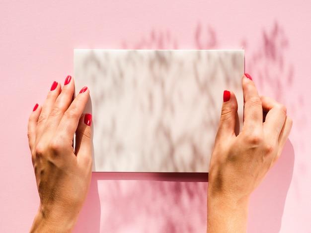 Mãos de close-up, segurando o papel com maquete