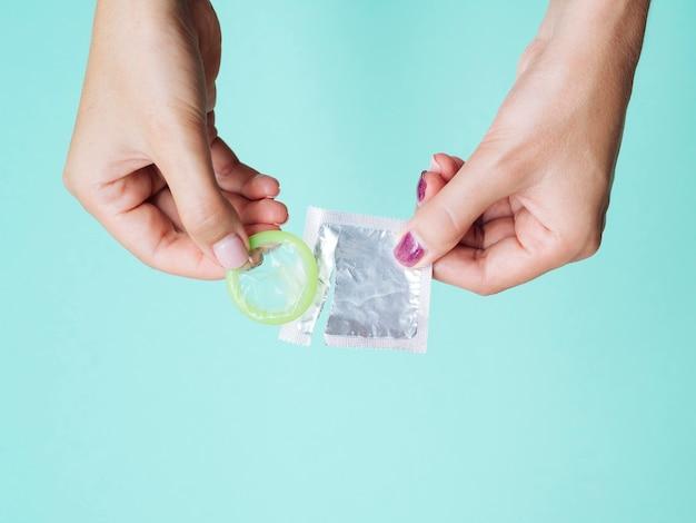Mãos de close-up, segurando o preservativo desembrulhado