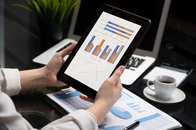 Mãos de close-up, segurando o tablet, documentos financeiros