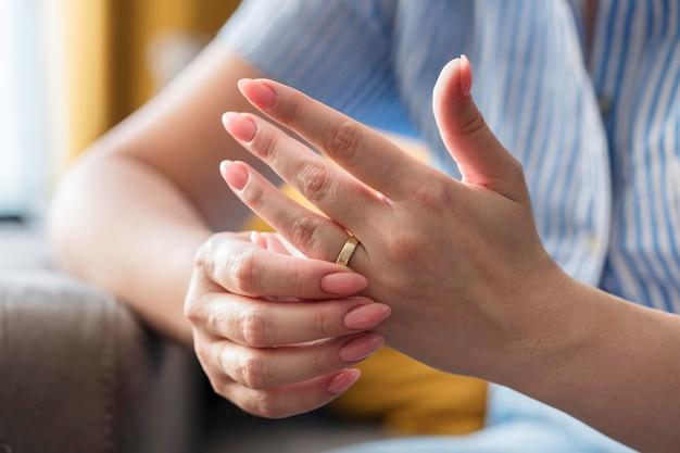 Mãos de close-up usando anel de casamento