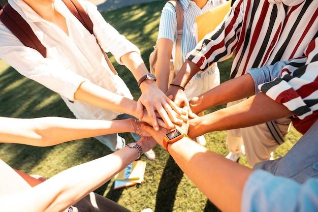 Mãos de colegas de grupo deitadas umas sobre as outras formando um círculo