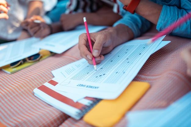 Mãos de colegas de grupo segurando lápis treinando para os testes