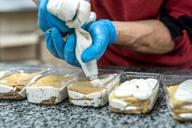 Mãos de confeiteiro com saco de confeitar decorando sobremesas deliciosas