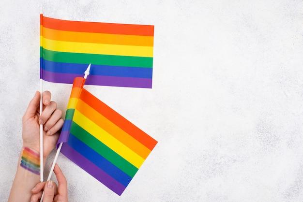Mãos de cópia-espaço com bandeiras do dia do orgulho