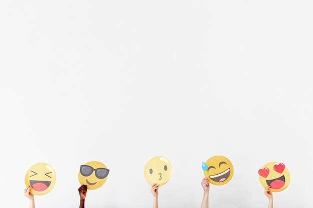 Mãos de cópia-espaço com diferentes emoji