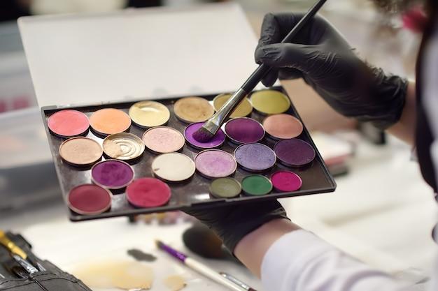 Mãos de cosmetologista com paleta de sombra para os olhos em close-up do salão de beleza.