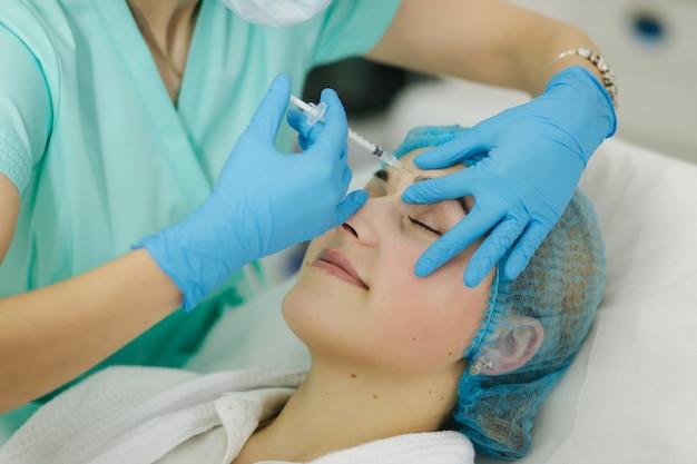Mãos de cosmetologista fazendo injeção no rosto, lábios