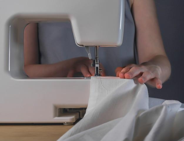 Mãos de costureira com pano de linho no processo de trabalho da máquina de costura com tecido de algodão natural orgânico