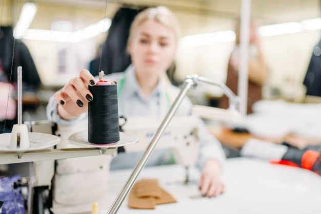 Mãos de costureira costuram tecidos em uma máquina de costura
