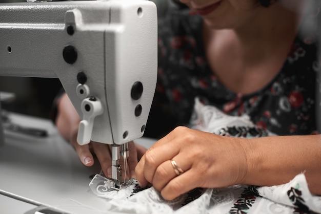 Mãos de costureira costurando em máquina moderna