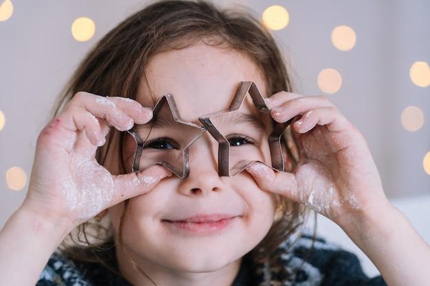 Mãos de criança close-up preparando biscoitos usando cortadores de biscoito.
