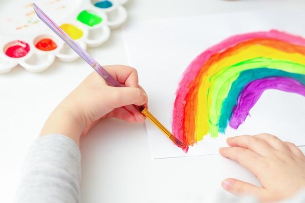 Mãos de criança, desenho de arco-íris.