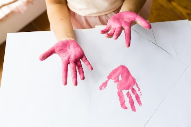 Mãos de criança e impressão rosa cor