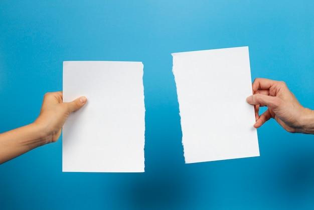 Mãos de criança e mulher segurando pedaços de folha de papel branco rasgado em azul claro