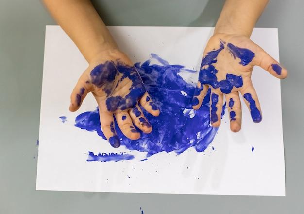 Mãos de criança em tinta azul conceito de desenvolvimento precoce arte, educação criativa e pré-escolar para foco suave de crianças