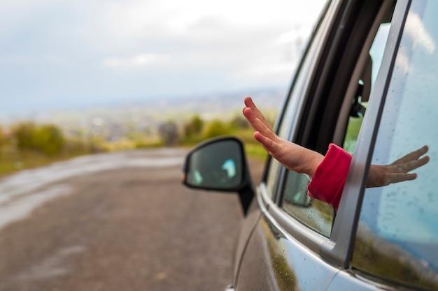 Mãos de criança em uma janela de carro durante a viagem de férias