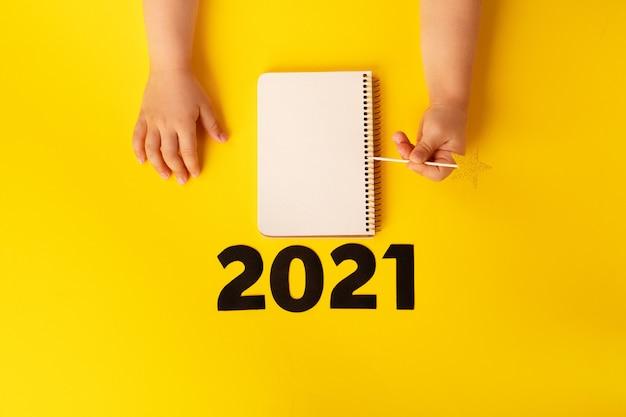 Mãos de criança escrevendo no caderno aberto, 2021 números em amarelo. vista de cima, copie o espaço