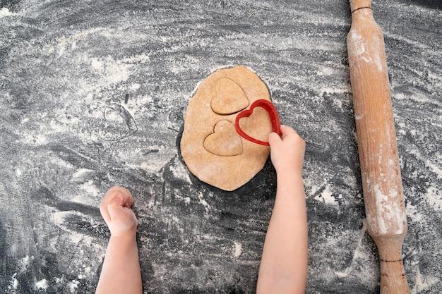 Mãos de criança fazendo biscoitos amanteigados na mesa com farinha