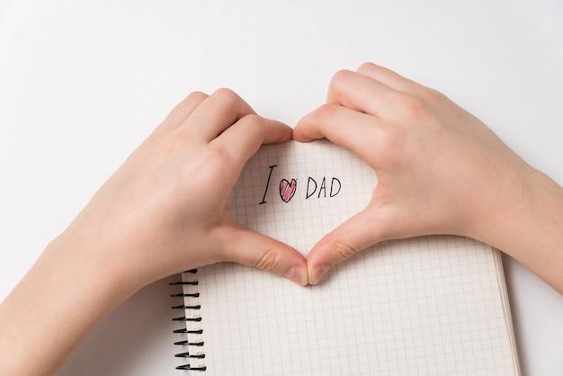Mãos de criança fazendo formato de coração com eu amo o pai aviso. caderno com manuscrito. dia dos pais.