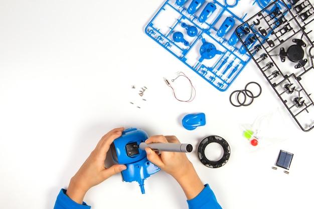 Mãos de criança fazendo robô azul na mesa branca.