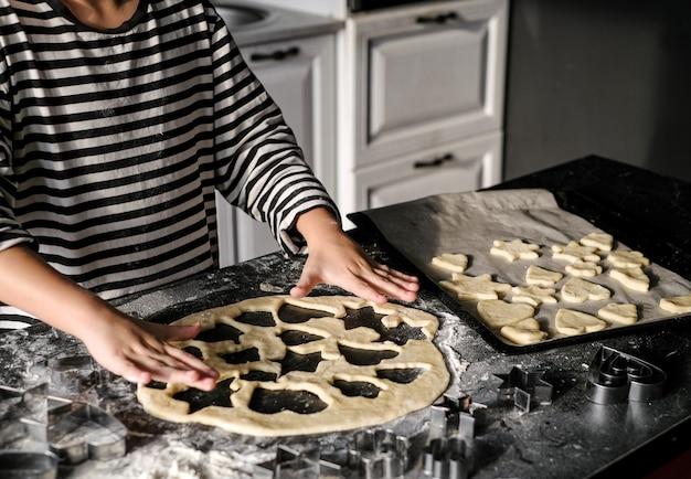 Mãos de criança fazendo um bolo de natal na cozinha com formulários