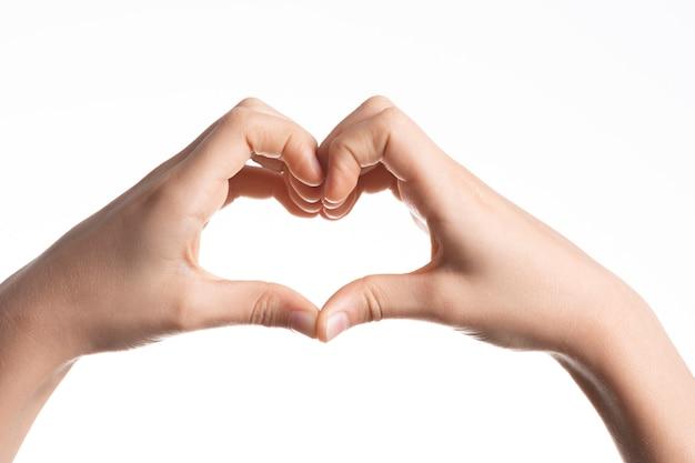 Mãos de criança formando um coração