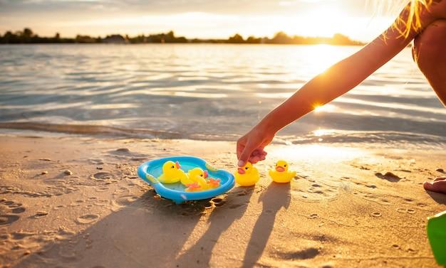 Mãos de criança irreconhecível caucasiana brincando com patos amarelos de borracha