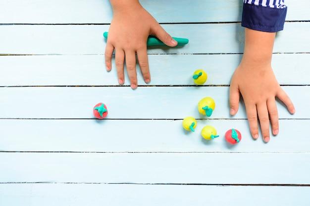 Mãos de criança moldando argila e usando a criatividade para fazer linha e frutas