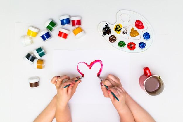 Mãos de criança pintando um coração