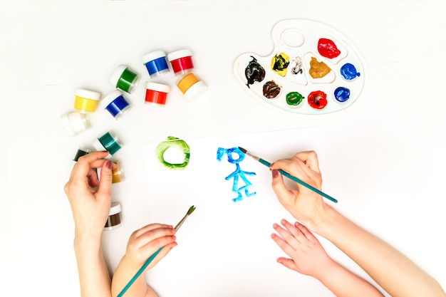 Mãos de criança pintando uma família