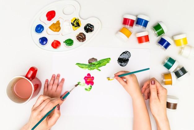 Mãos de criança pintando uma flor