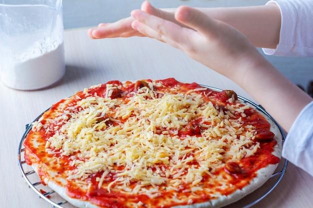 Mãos de criança polvilhe queijo na massa de pizza