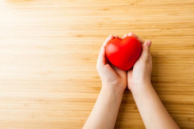 Mãos de criança segurando coração vermelho, cuidados de saúde, doar e conceito de seguro familiar