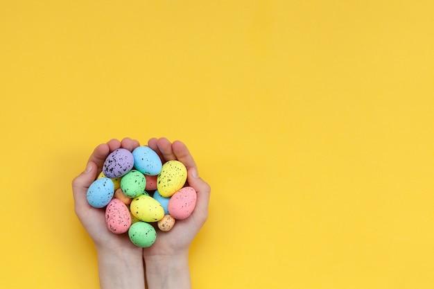 Mãos de criança segurando ovos de páscoa pintados coloridos sobre fundo amarelo. conceito de feliz páscoa.