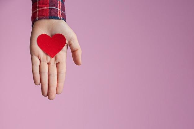 Mãos de criança segurando um coração de papel vermelho nas mãos no fundo rosa. dia dos namorados, dia das mães e conceitos de amor.