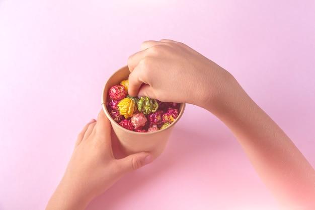 Mãos de criança segurando uma caixa com pipoca de doce de caramelo colorido arco-íris em fundo rosa. conceito de lanche de cinema. assistindo filme e entretenimento. colocação plana.