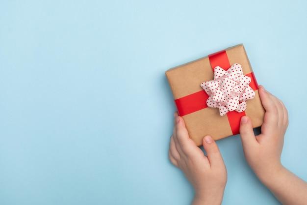 Mãos de criança segurando uma caixa de presente em fundo azul