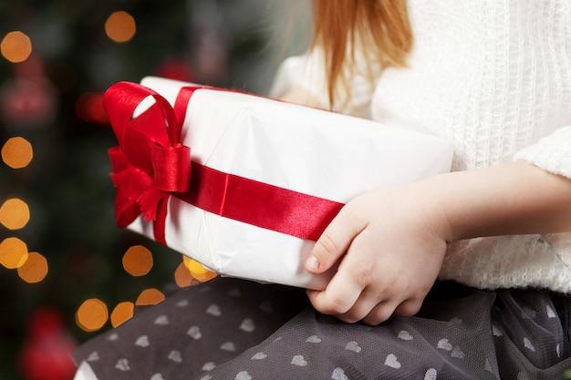 Mãos de criança segurando uma caixa de presente. natal, ano novo, conceito de aniversário. fundo festivo com bokeh e luz solar. conto de fadas mágico