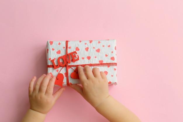 Mãos de criança segurando uma linda caixa de presente em fundo rosa