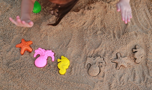 Mãos de crianças close-up jogando areia com bloco animal formando na praia.