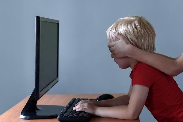 Mãos de crianças coloca os olhos para um menino que usa um computador