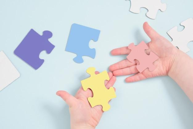 Mãos de crianças coloridas segurando quebra-cabeças na superfície azul
