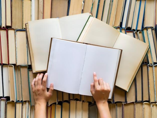Mãos de crianças com livros. a criança está estudando ciências. conceito de conhecimento e sabedoria.